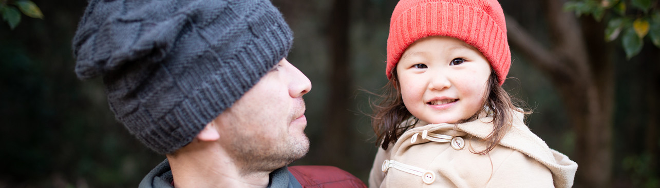 man holding young girl; wearing toques