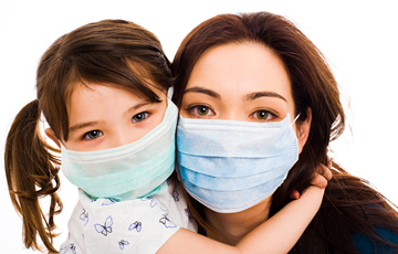 mother and daughter wearing surgical masks
