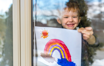 young boy inside holding picture of a rainbow
