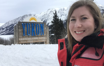 Field epidemiologist Courtney Rady Smith in front of Yukon sign