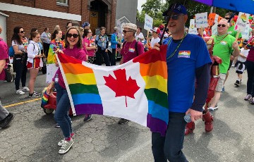 people marching in pride parade holding flag