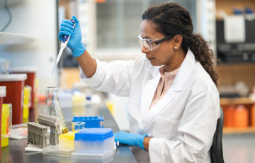 Woman uses pipette to test sample in lab