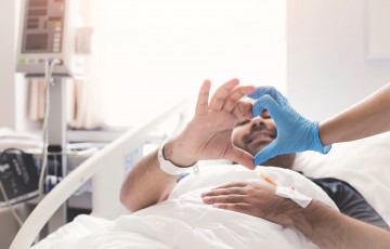 Man in hospital bed making heart shape with his hands and that of a care provider