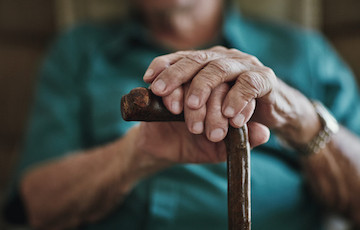 older figure with hands on a cane