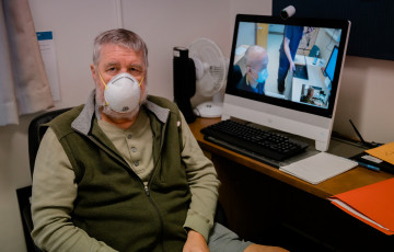 Alan Holt siting in front of a computer screen wearing a medical mask